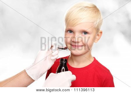 A delicious syrup, the boy drink a cure for the common cold.