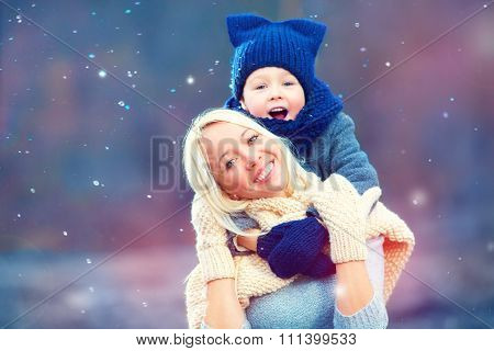 Happy Woman And Kid Emracing Under Winter Snow