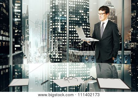 Businessman With Laptop In Modern Office With Night Megapolis City View
