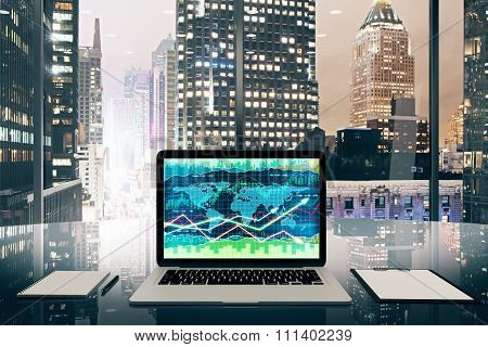 Business Graph On Laptop Screen On Glassy Table In Modern Office With Night Megapolis City View
