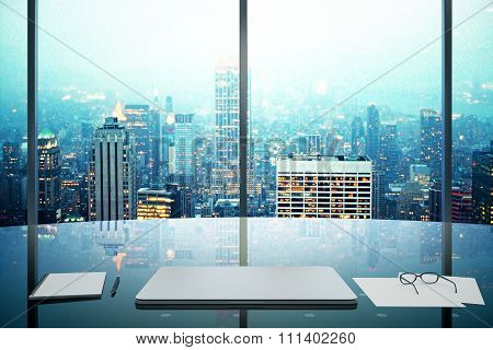 Modern Office With Glassy Table, Laptop And Night Megapolis City View