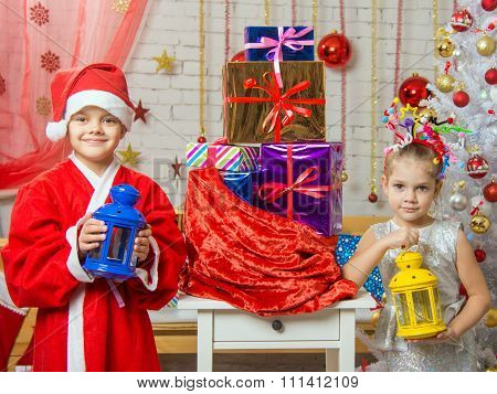 Two Girls In Christmas Costumes Are With Candlesticks From The Bag With Christmas Gifts