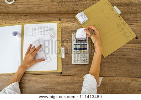 Top View Of Female Accountant Making Calculations Using Adding Machine