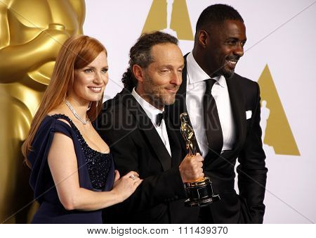 Jessica Chastain, Emmanuel Lubezki and actor Idris Elba pose in the press room during the 87th Annual Academy Awards at Loews Hollywood Hotel on February 22, 2015 in Hollywood, California.