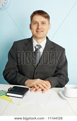 Businessman Sitting In An Office At Table