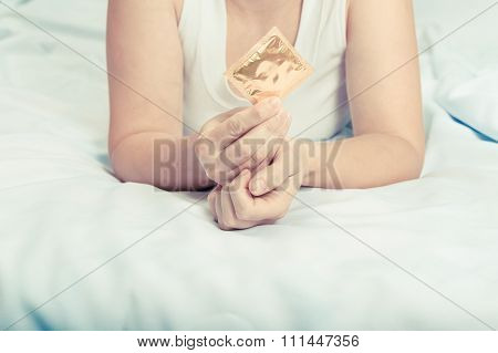 Young Caucasian Woman On  Bed Gives A Condom.