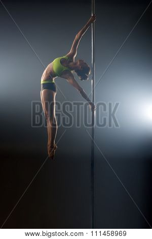 Pole dance. Graceful dancer performs acrobatic pas