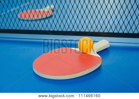 Pingpong Rackets And Ball And Net On A Blue Pingpong Table