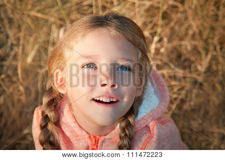 Portrait Of A Little Girl With Blue Eyes And Pigtails