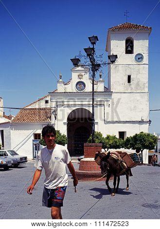 Man and donkey by church, Monda.