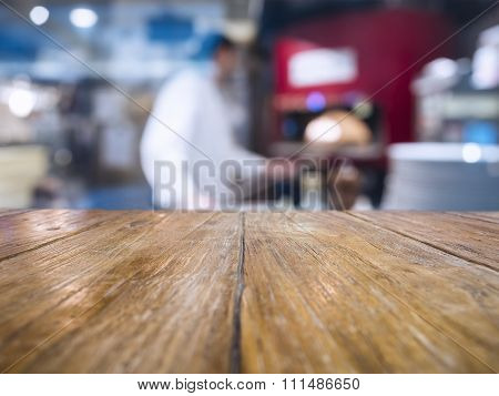 Table Top With Blurred Chef Cooking Pizza Restaurant Background