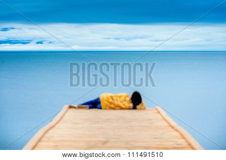 Woman Sitting On The Wooden Pier And Looking At Lake Baikal.