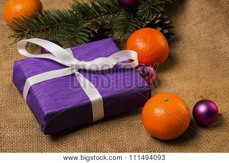 Purple Gift With White Ribbon And Christmas Decorations