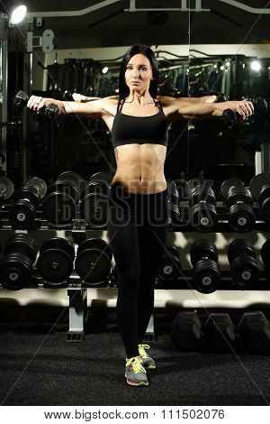sexy woman doing workout with dumbbells  in gym, exercise for the shoulders