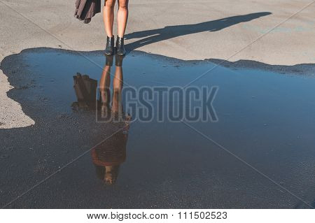 Puddle Reflecting A Beautiful Girl Posing In An Urban Context