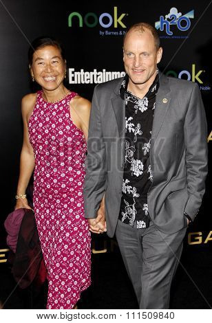 Woody Harrelson and Laura Louie at the Los Angeles premiere of 'The Hunger Games' held at the Nokia Theatre L.A. Live in Los Angeles on March 12, 2012.