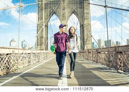 Young Couple Walking On The Brooklyn Bridge