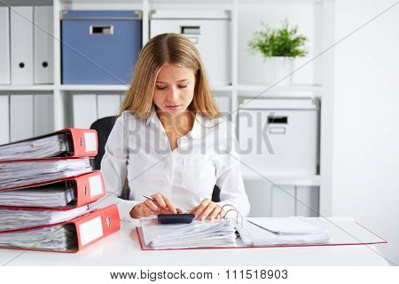Young Business Woman Calculates Tax At Desk In Office
