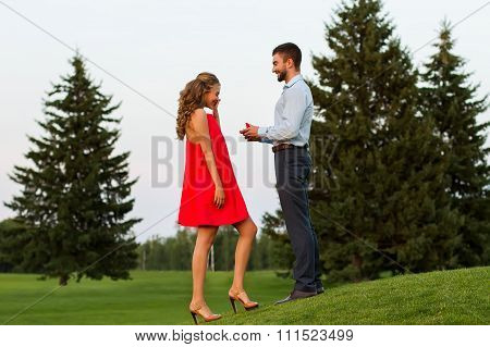 Guy doing the girl proposal in the middle of a beautiful park.