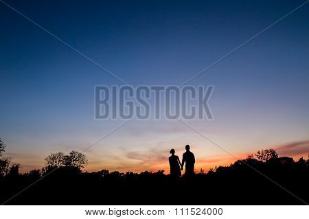 Couple in love walking at sunset.