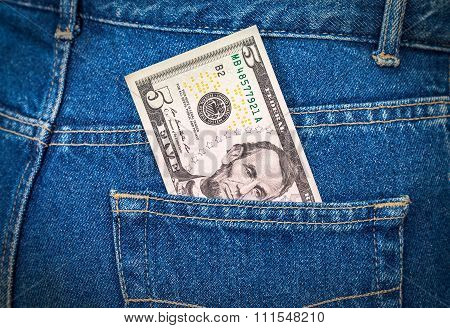 Five Dollars Bill Sticking Out Of The Blue Jeans Pocket