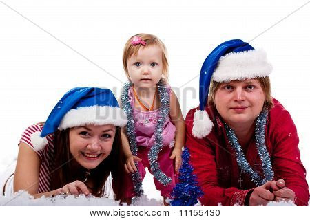 Family In Santa's Hat Lying In Artificial Snow