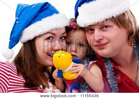 Family In Santa's Hat Sitting In Artificial Snow