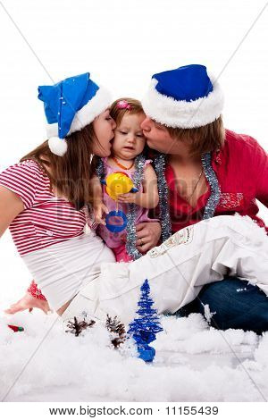 Parents In Santa's Hat Kissing Their Child In Artificial Snow