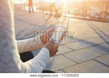 Female chatting in network on cell telephone while sitting near sea port