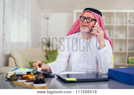 Arabian business man in his home office using smart phone