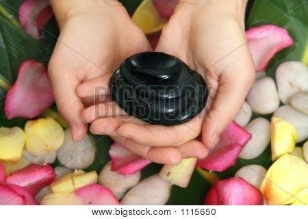 Hands Holding Basalt Stones