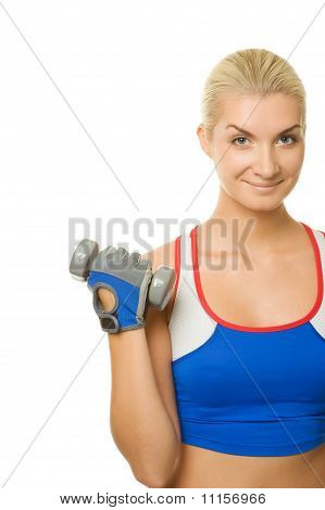 Beautiful young fitness trainer with two dumbbells