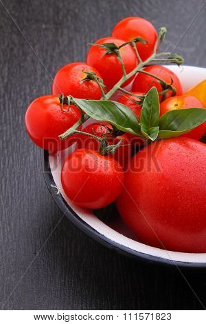 Red And Yellow Tomatoes In A White Bowl