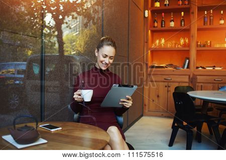 Female watching movie on touch pad while breakfast in coffee shop