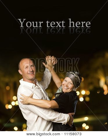 Middle-aged happy couple dancing waltz at night