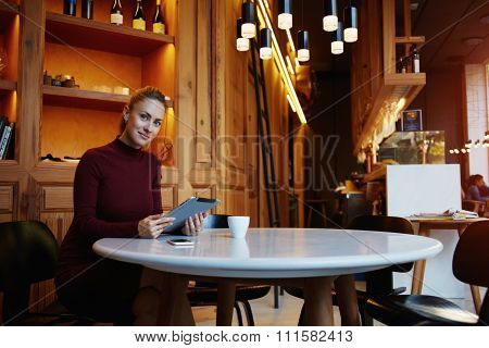 Beautiful woman posing while sitting with touch pad in modern coffee shop interior during work break