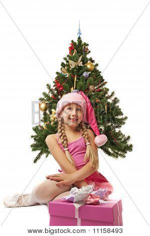 Happy Santa girl near the christmas tree