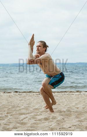 Man Practices Yoga On A Sandy Beach