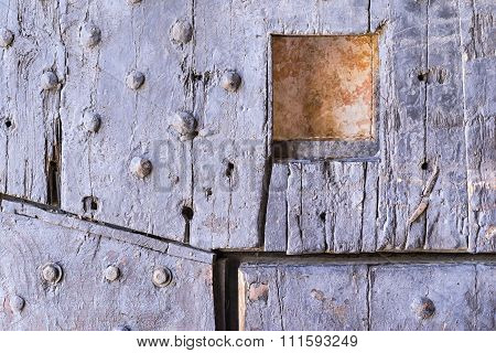Old Wooden Riveted Gate Of Fortress With A Loophole