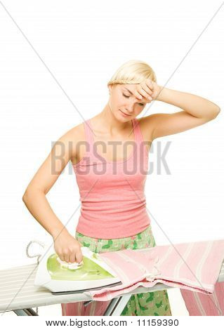 Beautiful young woman ironing clothes at home