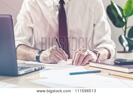 Businessman Working Overtime At Office Desk