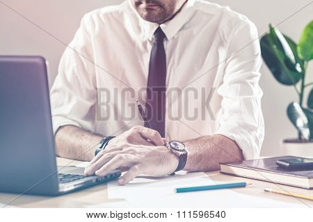 Businessman Writing Notes And Using Laptop At Office Desk