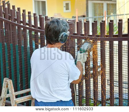 Worker Cuts Iron Bars With Grinder