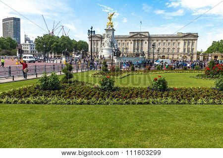 Tourists Gather At The Gates Of Buckingham Palace And The Base Of The Victoria Monument.