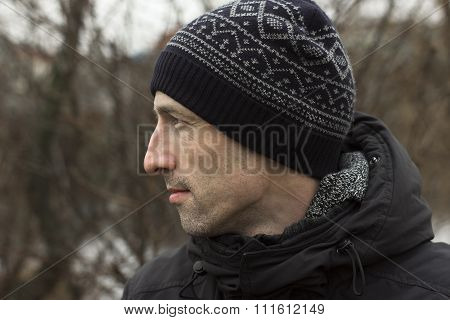 A man in a knitted cap and a black jacket