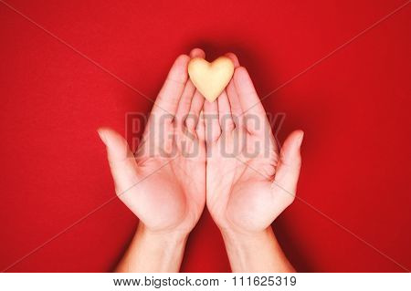 Two hands, holding little wooden heart genly