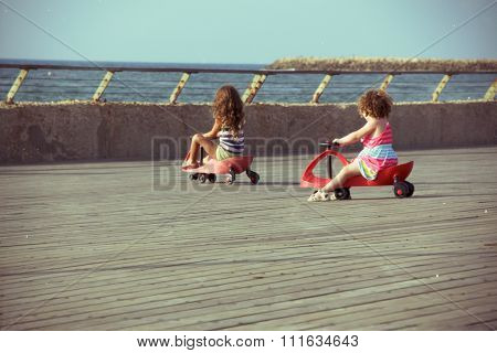 Two little girls riding on toy car (Swing Car \ Bimba) on the jetty by the sea