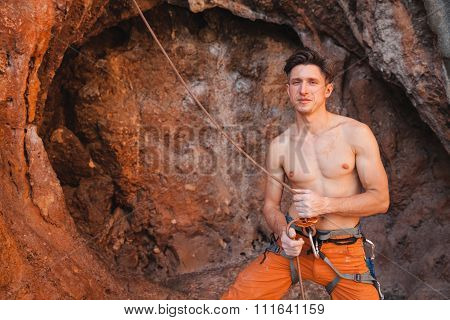 Rock climber holding belay rope against the rock