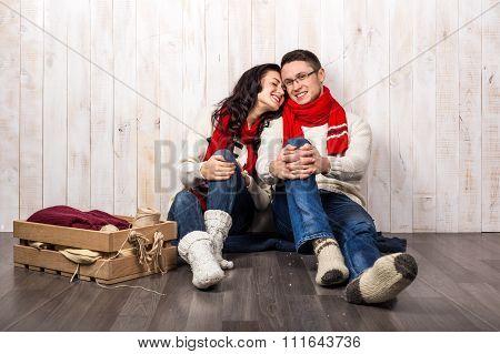 Nice love couple sitting on carpet Christmas style
