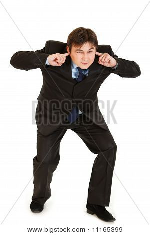 Young businessman ducking in fear and closing ears with fingers isolated on white